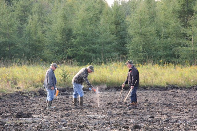 Placing stakes to mark boundaries at Walker Wetlands pond