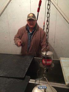 Volunteer adjusting fish feeders in hatchery